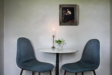 Limewash walls with blue dining chairs and table.