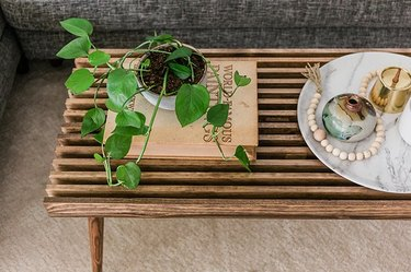 Slat wood coffee table with plant and marble tray on top.