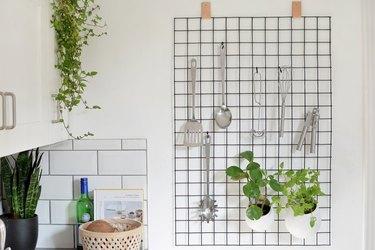 Grid wall organizer with kitchen utensils.