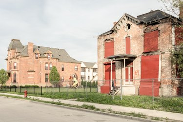large red brick home with playground next to abandoned home with boarded windows