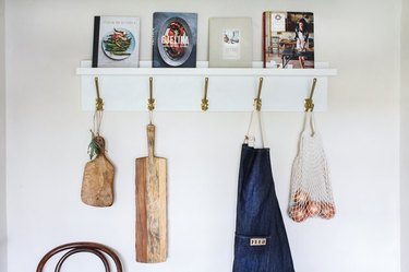 Wall shelf with hooks, holding cookbooks and cutting boards.