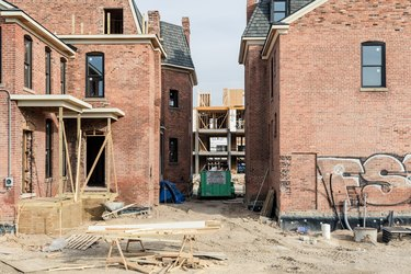 unfinished construction project on red brick home surrounded by dirt and wood