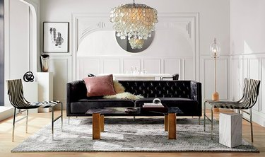 living room with black sofa, chandelier and two chairs