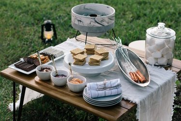 S'mores station set up in backyard on table.