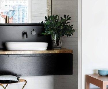 Wood painted a sleek black makes for a modern wood backsplash style.