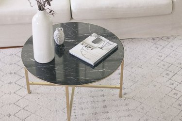 Marble top coffee table with brass legs in living room.