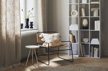 white bookshelf near cane chair and window with black vases
