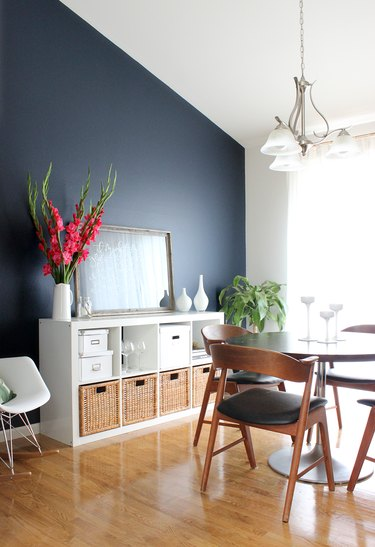 blue dining room with round table and bookcase for storage