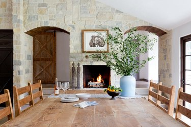rustic dining room with stone fireplace and farmhouse table