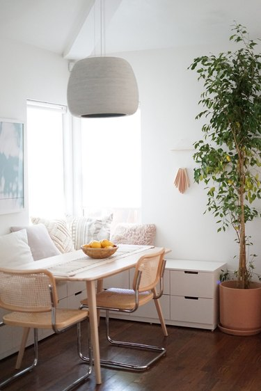 dining room area with white banquette and wicker chairs