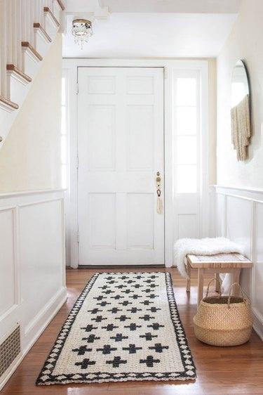 white hallway with handpainted jute rug