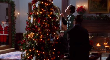 two figures near a Christmas tree