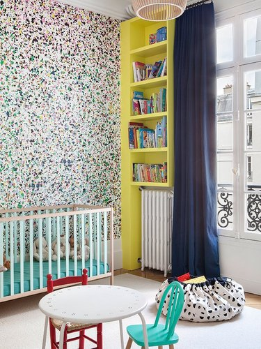 Modern nursery with paint splatter pattern wallpaper, yellow built-in shelves, modern crib, bean bag.