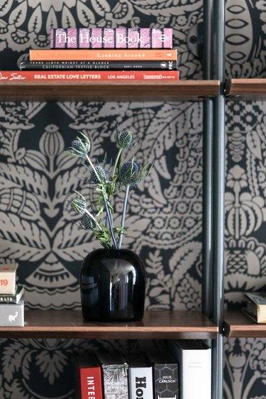 Dark printed wallpaper behind bookshelf with black vase.