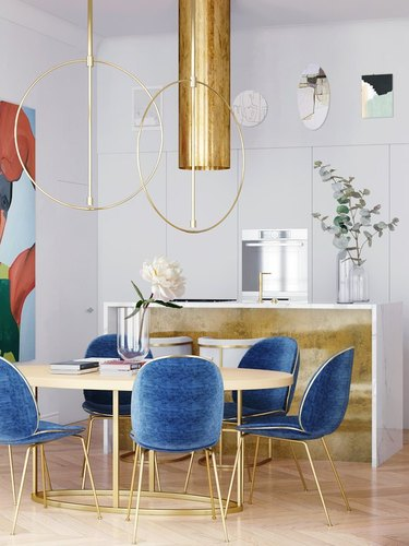 Gold ceiling light over dining table with blue chairs.