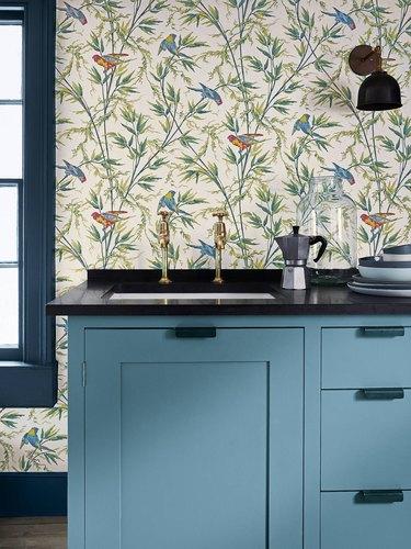 kitchen wallpaper backsplash idea with subtle botanical and bird pattern and blue cabinets