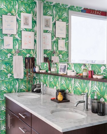 Green palm print wallpaper in bathroom with two sinks.