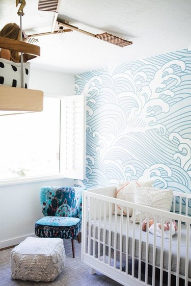 Modern nursery with wave pattern wallpaper, blue chair, white crib.