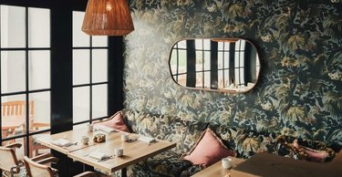 Dining room with dramatic print wallpaper and mirror on wall.
