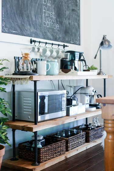 Farmhouse coffee bar with industrial pipes, wood shelves, and small kitchen appliances