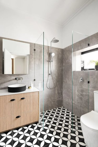 modern shower window idea with black and white patterned floor tile and faux wood vanity