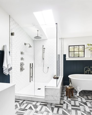shower window idea with skylight in navy and white bathroom with clawfoot tub