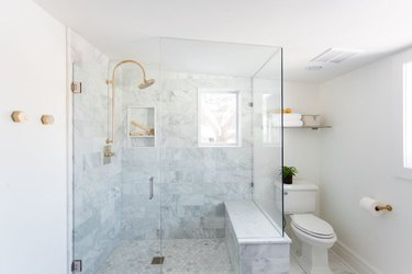shower window idea in brass and marble bathroom with shower seat and shower window