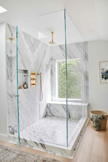 shower window idea in marble and brass bathroom with oversized shower window