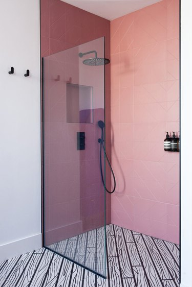 black rain showerhead in pink tile shower