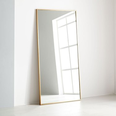 Oversized rectangular leaning floor mirror with thin brass border