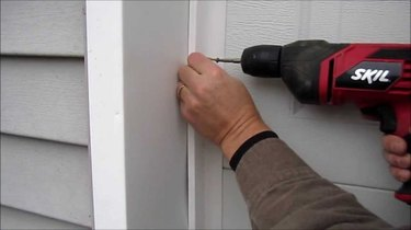Installing garage door weatherstripping.