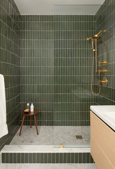 vertical green subway tile shower idea with gold fixtures