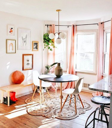 Breakfast nook with black and white midcentury dining furniture, jute doily rug, and peach curtains
