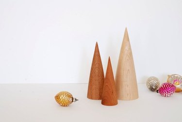 Three small minimal wooden Christmas trees in various finishes