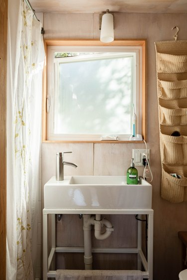 view of standing bathroom sink in front of an open window; electrical outlet with electric toothbrush plugged in