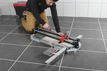 Cutting tile on the floor.