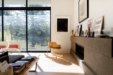 living room with rocking chair, large windows, fireplace