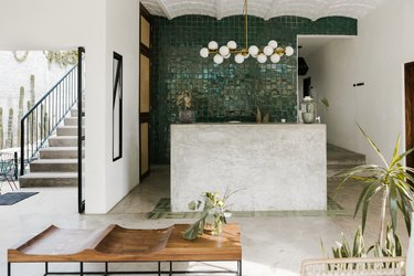 open entryway space leading to outdoors with concrete floors, tiled wall, scalloped ceiling