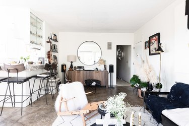 living room with concrete floors and rug leading into dining room