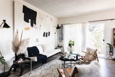 living room with French doors covered with a sheer curtain, concrete floors, white patterned rug