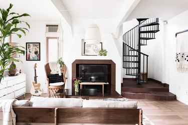 living room with fireplace, spiral staircase, large plant, guitar