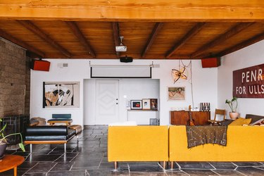 living room with wooden ceilings, yellow couch, slate floor