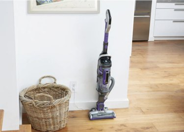 focus on vacuum and wicker basket against white wall