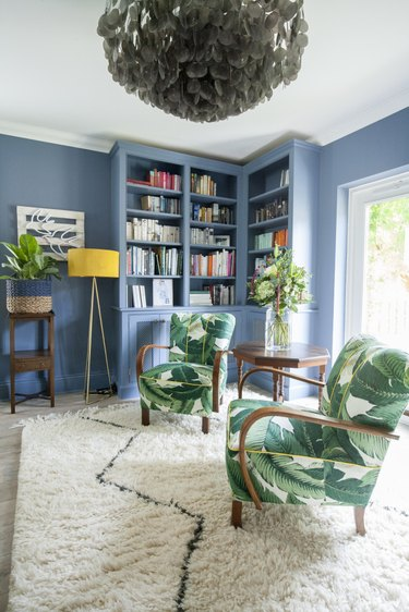 Blue bookcase blending in to blue living room walls with white shag carpet