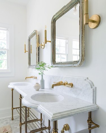 white bathroom countertop with traditional beveled in marble with console sinks and brass fixtures