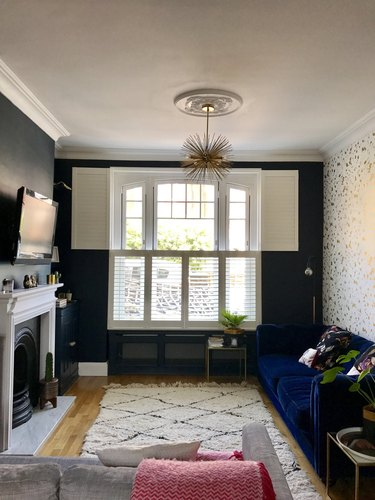 Dark blue living room with gold accents and blue velvet sofa