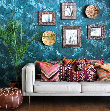 Bohemian blue living room with tropical wallpaper and patterned throw pillows