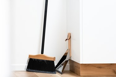 Broom and dust pan on wood floor