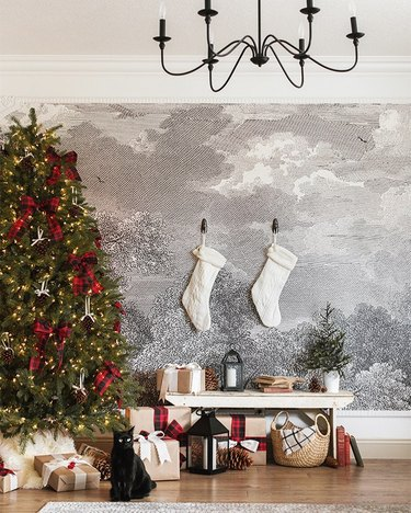 farmhouse Christmas tree idea with red bows in front of wall mural