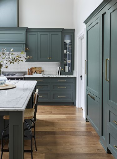 Teal kitchen idea with painted cabinets, hardwood floor, and marble countertops